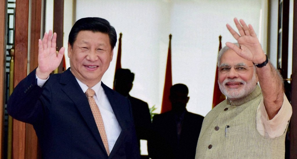Ahmedabad: Prime Minister Narendra Modi waves along with Chinese President Xi Jinping as he welcomes him upon his arrival at a hotel in Ahmadabad on Wednesday. PTI Photo (PTI9_17_2014_000127B)