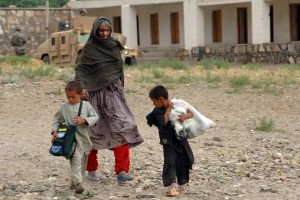 An Afghan woman walks home with her children carrying humanitarian goods in the Kapisa province of Afghanistan. Credit: US Army