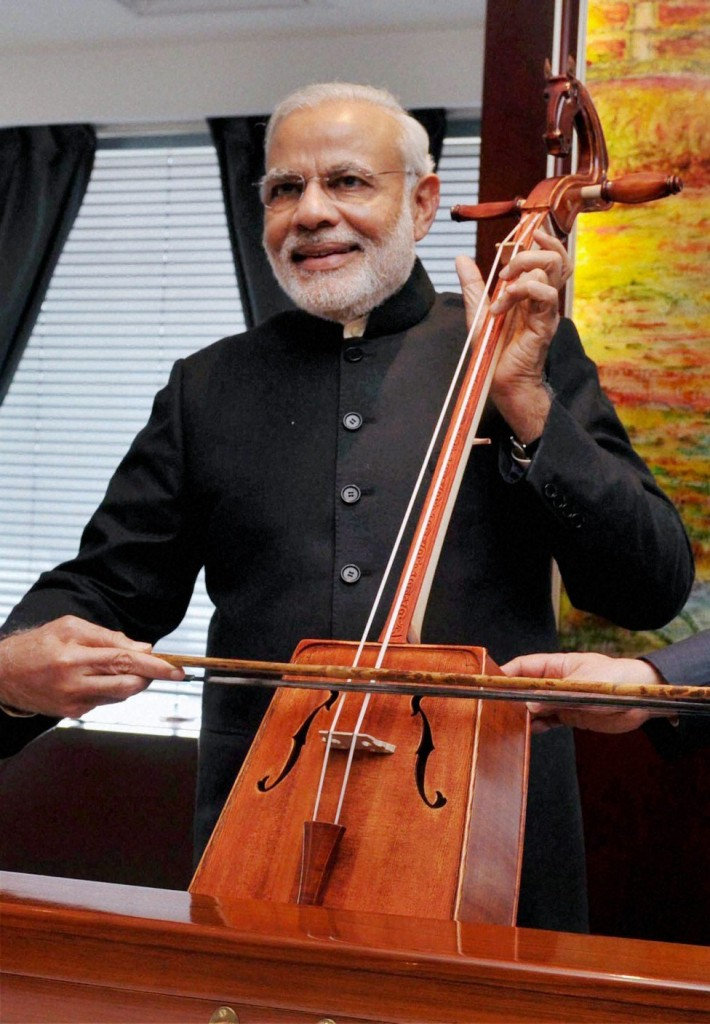 Watch Me Fiddle: Prime Minister Narendra Modi tries his hand with a musical instrument in Mongolia in May 2015. Photo: PTI