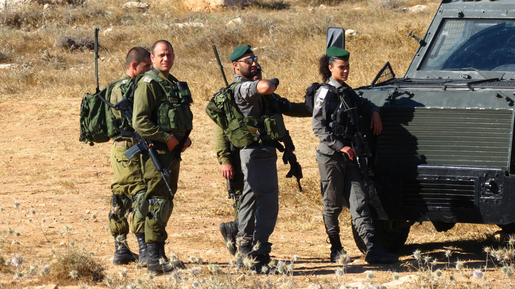 As Israeli soldiers look on, a group of Palestinian and Israeli activists pleacefully reclaim for a Palestinian family what is rightfully theirs. South Hebron. Credit: Guy Batavia