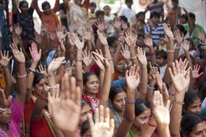 Community members in a local slum participate in discussions after watching video documentaries screened by the Self Employed Women's Association of India. Credit: Gates Foundation