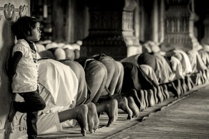A little girl lost in thoughts as Muslim men pray nearby. Credit: tataimitra/Flickr, CC BY 2.0