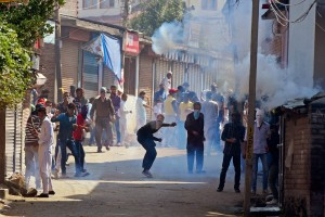 Protesters hurl stones at security personnel amid tear gas after a protest over the beef ban, near Eidgah in Srinagar on Friday. Credit: PTI Photo