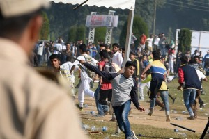 Youths throw stones and water bottles on police at the venue as violent clashes erupted during the first ever International Kashmir half-Marathon at Kashmir University Campus in Srinagar on Sunday. Credit: PTI Photo
