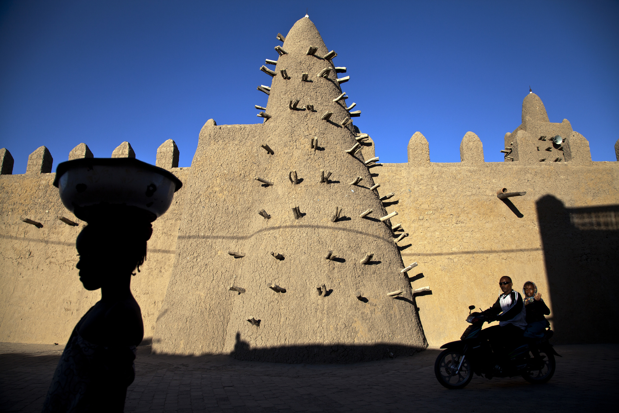 Residents of Timbuktu pass by the Djingareyber Mosque. The mosque is one of the historical architectural structures (along with Sankore Mosque, Sidi Yahia Mosque and sixteen mausoleums and holy public places) which together earned Timbuktu the designation of World Heritage Site by UNESCO. Credit: UN Photo/Marco Dormino