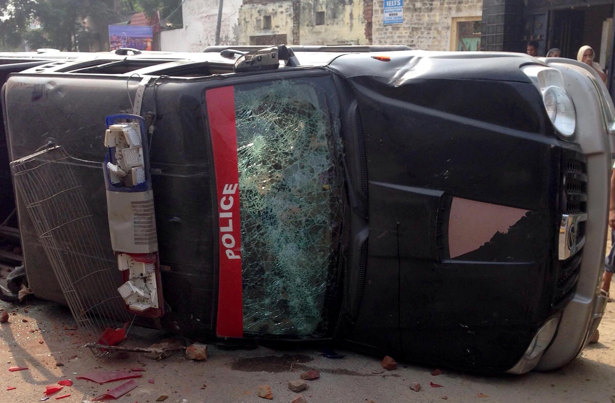 A police van destroyed by protestors. Credit: IANS