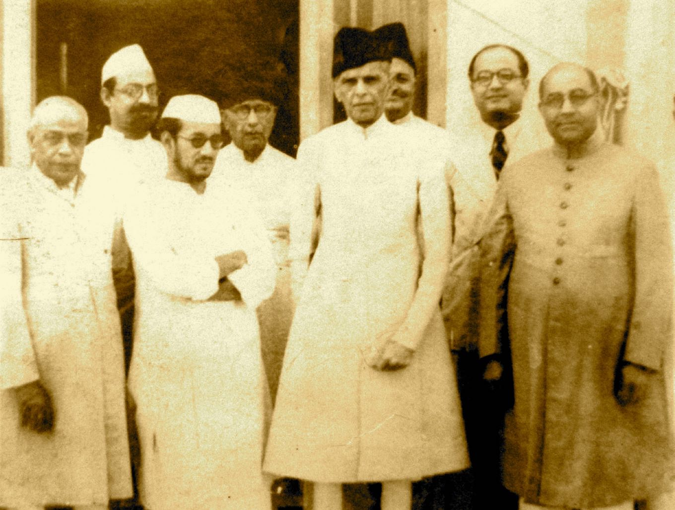 From Left to Right: Nawab Ismail Khan (President U.P. Muslim League), Syed Hussain Imam, Raja of Mahmudabad, Chaudhry Khaliquzzaman, M. A. Jinnah, Saadullah Khan (behind Jinnah), M. A. H. Ispahani, and Nawabzada Liaquat Ali Khan, 1942 Credit: National Archives of Pakistan, Islamabad