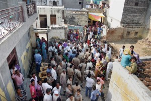 Security personnel and people gather outside the house of Jai Prakash who was found dead under mysterious conditions at Bisara village where Mohammad Akhlaq was lynched by a mob after rumours of beef eating, in Dadri on Tuesday. Credit: PTI Photo by Atul Yadav