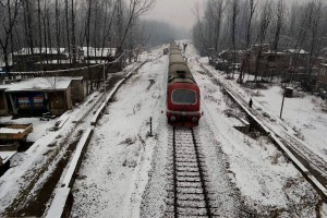 A snow-covered train moves on Srinagar- Qazigund railway track in Anantnag district on Sunday. Credit: PTI