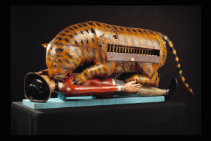 """Tippoo's Tiger"" was made for Tipu Sultan, ruler of Mysore in South India (1782-1799). The almost life-size wooden semi-automaton consists of a tiger mauling a prostrate figure in European clothes. An organ is concealed inside the tiger's body, and when a handle at the side is turned, the organ can be played and the man's arm simultaneously lifts up and down. Intermittent noises are supposed to imitate the wails of the dying man.  The tiger was discovered by the British in the palace at Tipu Sultan's capital after the Siege of Seringapatam in 1799. The invading army stormed through a breach in the ramparts and, in the ensuing chaos, Tipu and a great many of his soldiers, generals and the citizens of the town were killed. The victorious troops then rampaged through the city, looting valuables from the palace and from private houses. Credit: Victoria and Albert Museum, London."
