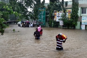 Patients and their care-takers shift from a flooded hospital after heavy rains in Chennai on Tuesday. Credit: PTI