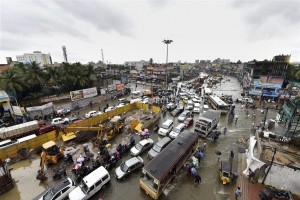 A vehicle moves on a water-lodged road during heavy rains in Chennai on Wednesday. Credit: PTI