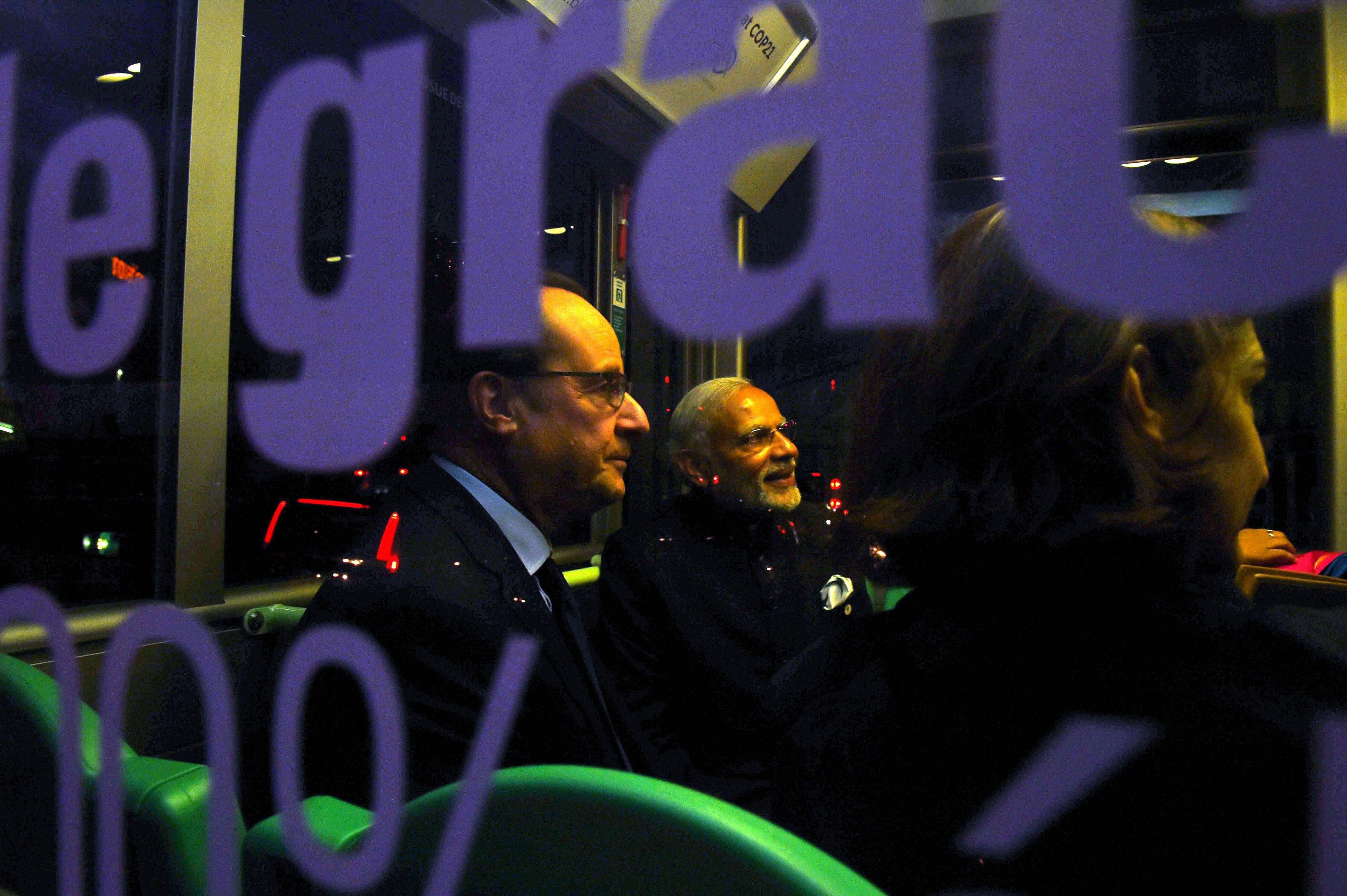 Prime Minister Narendra Modi with French President Francois Hollande sitting in the shuttle bus for an event at COP21, the United Nations Climate Change Conference, in Le Bourget, outside Paris, on Monday. Credit: PTI Photo by Atul Yadav