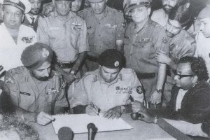 Major Gen JFR Jacob (standing right behind Gen Niazi)  witnessing the instrument of surrender in Dhaka in December 1971. Credit: Wikipedia Commons