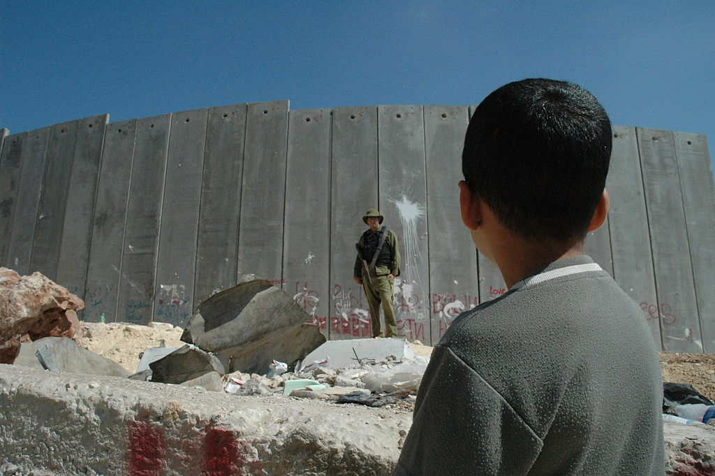 File picture of Palestinian boy looking at an Israeli soldier along the wall Wikipedia commons