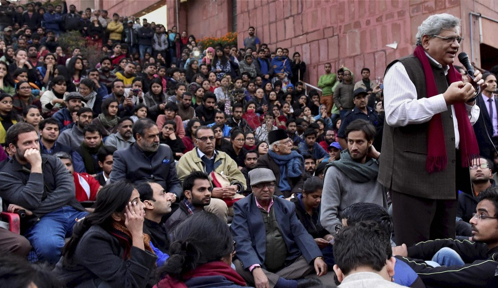 General Secretary of CPI(M) Sitaram Yechury addresses Jawaharlal Nehru University students as Congress vice president Rahul Gandhi (L) looks on, in New Delhi on Saturday. Yechury and Gandhi went to the campus to meet the students protesting for the release of Student Union president Kanhaiya Kumar. Credit: PTI Photo by Kamal Kishore