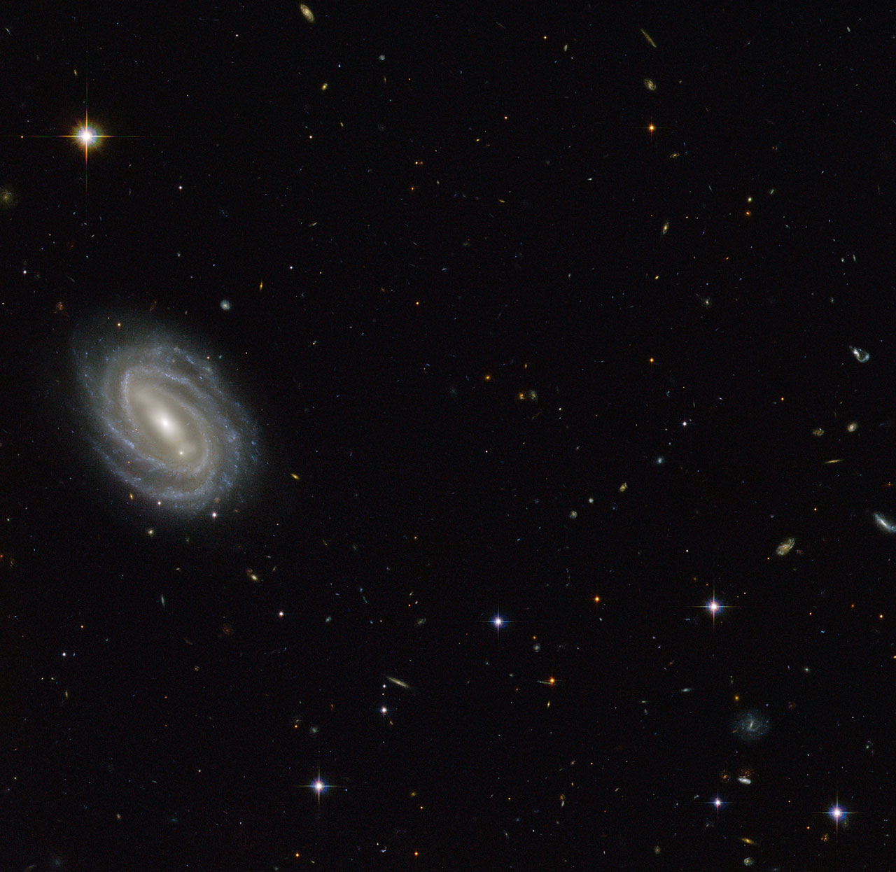This new NASA/ESA Hubble Space Telescope image shows a beautiful spiral galaxy known as PGC 54493, located in the constellation of Serpens (The Serpent). This galaxy is part of a galaxy cluster that has been studied by astronomers exploring an intriguing phenomenon known as weak gravitational lensing. This effect, caused by the uneven distribution of matter (including dark matter) throughout the Universe, has been explored via surveys such as the Hubble Medium Deep Survey. Dark matter is one of the great mysteries in cosmology. Credit: gsfc/Flickr, CC BY 2.0