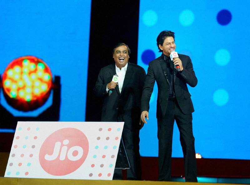 Laughing all the way to the bank. Mukesh Ambani at a Reliance Jio publicity event with the actor Shahrukh Khan. Credit: PTI