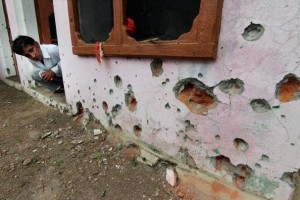 A man looks at the mortar shell marks on the wall of his house. Credit: PTI