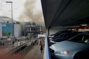 People walk away from Brussels airport after explosions rocked the facility in Brussels, Belgium Tuesday. Credit: PTI