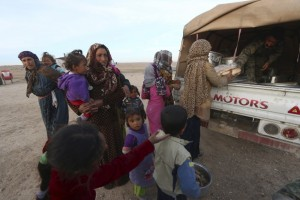 Fighters from the Democratic Forces of Syria distribute food aid to internally displaced Syrians that fled the town of Sabaa Zlam in the southwestern countryside of Hasaka, Syria, February 17, 2016. Credit: Reuters/Rodi Said