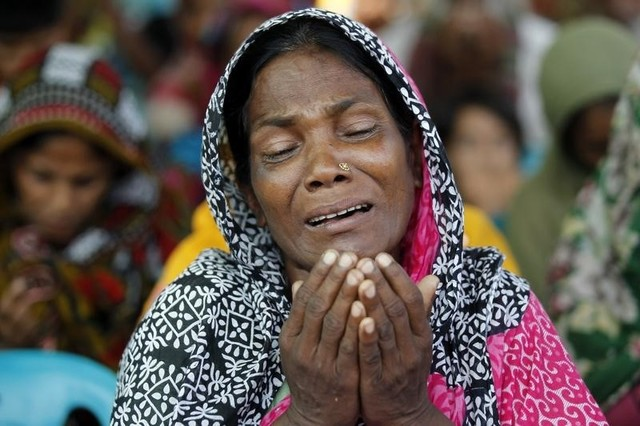 A relative of a garment worker, who went missing in the Rana Plaza collapse, takes part in a mass prayer on the first year anniversary of the accident, at a school in Savar April 24, 2014. Credit: Reuters/Andrew Biraj