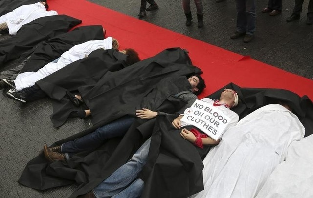 Activists stage a protest acting out a scene where actors portraying as victims, lie along a red carpet in a shopping district in central Brussels, to mark the first anniversary of the Rana Plaza factory collapse April 24, 2014. Credit: Reuters/Francois Lenoir
