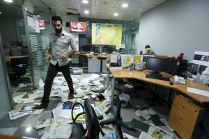 An employee walks on newspapers after protesters attacked the office of Saudi-owned newspaper Asharq al-Awsat in Beirut, Lebanon, in this April 1, 2016 file photo. Credit: REUTERS/Mohamed Azakir/Files