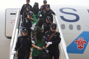 Police escort a group of people wanted for suspected fraud in China, after they were deported from Kenya, as they get off a plane after arriving at Beijing Capital International Airport in Beijing, China, April 13, 2016. Credit: Reuters