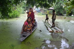 Villagers commute in local boats in a flooded village in the Morigaon district. Credit: PTI