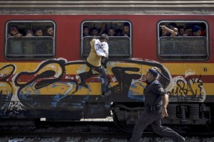 A policeman tries to stop a migrant from boarding a train through a window at Gevgelija train station in Macedonia, close to the border with Greece, August 15, 2015. Credit: Reuters