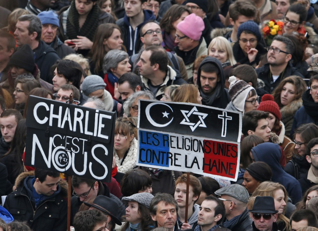 "Citizens carrying placards reading ""Charlie it is us"" and ""The religions united against the hatred"" take part in a French citizens solidarity march in Paris, January 11, 2015.  Credit: Reuters"