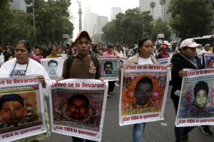 Relatives hold pictures of the missing students of Ayotzinapa College Raul Isidro Burgos during a march in Mexico City to mark the one-year anniversary of their disappearance on October 26, 2015. Credit: Reuters.