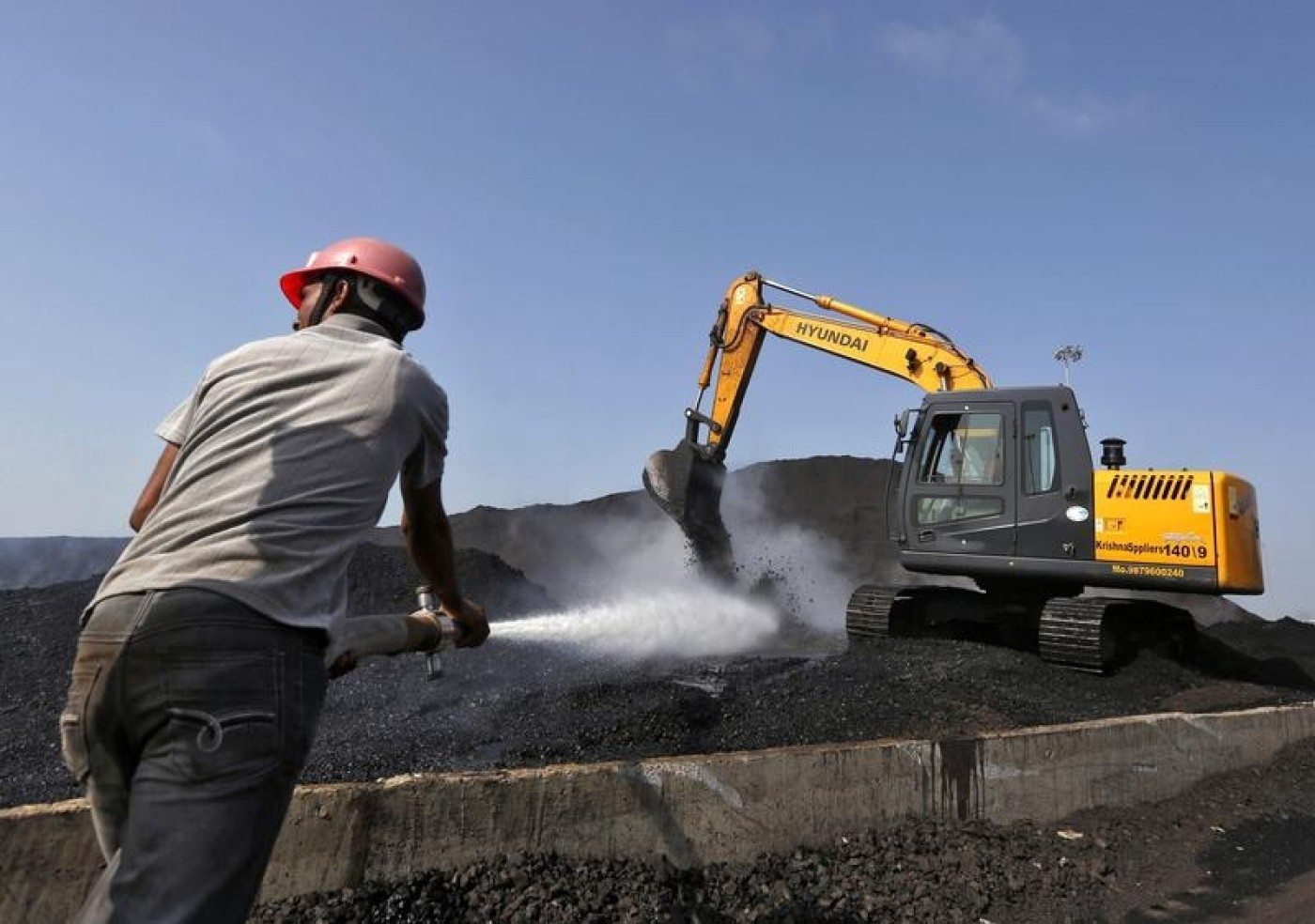 A worker sprays water over piles of coal as a bulldozer shifts coal at Mundra Port Coal Terminal in Gujarat. Credit: REUTERS/AMIT DAVE