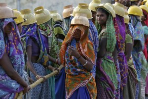 Women labourers wearing helmets take a break from laying underground electricity cables in Ahmedabad, India, March 7, 2016. Credit: Reuters/Amit Dave.