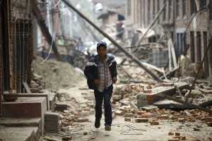 A man runs past damaged houses as aftershocks of an earthquake are felt a day after the earthquake in Bhaktapur, Nepal April 26, 2015. Rescuers dug with their bare hands and bodies piled up in Nepal on Sunday after the earthquake devastated the heavily crowded Kathmandu valley, killing at least 1,900, and triggered a deadly avalanche on Mount Everest. Credit: Reuters/Navesh Chitrakar.