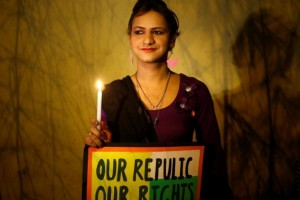 An LGBTQ rights activist holds a placard and a candle during a candlelight protest in New Delhi January 28, 2014. Credit: Reuters/Anindito Mukherjee/Files