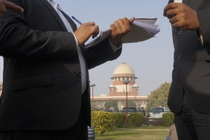 Lawyers confer against the backdrop of the Supreme Court. Credit: Shome Basu