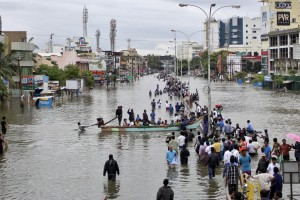 People travel on a boat as they move to safer places through a flooded road in Chennai, December 2, 2015. Credit: Reuters