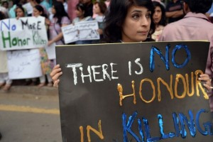 At a protest against 'honour killings', a woman holds a poster saying 'There is no honour in killing.' Credit: Reuters.