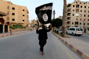 A member loyal to Islamic State waves a flag in Raqqa June 29, 2014. Credit: Reuters/Stringer/File Photo