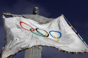 """The Olympic Flag flies in front of """"Christ the Redeemer"""" statue during a blessing ceremony in Rio de Janeiro August 19, 2012. Credit: Reuters/Ricardo Moraes"""