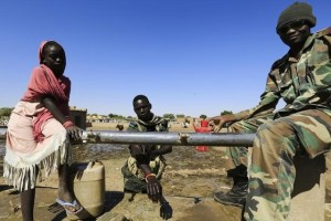Military personnel wash at a water station after arriving in Tabit village in North Darfur November 20, 2014. Credit: Reuters/Mohamed Nureldin Abdallah/Files
