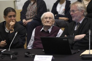 "Oskar Groening (C), defendant and former Nazi SS officer dubbed the ""bookkeeper of Auschwitz"", reacts as he sits between his lawyers Hans Holtermann (R) and Susanne Frangenberg (L) in the courtroom during the verdict of his trial in Lueneburg, Germany, July 15, 2015. The 94-year-old German man who worked as a bookkeeper at the Auschwitz death camp was convicted on Wednesday of being an accessory to the murder of 300,000 people and was sentenced to four years in prison, in what could be one of the last big Holocaust trials. Credit: REUTERS/Axel Heimken/Pool"
