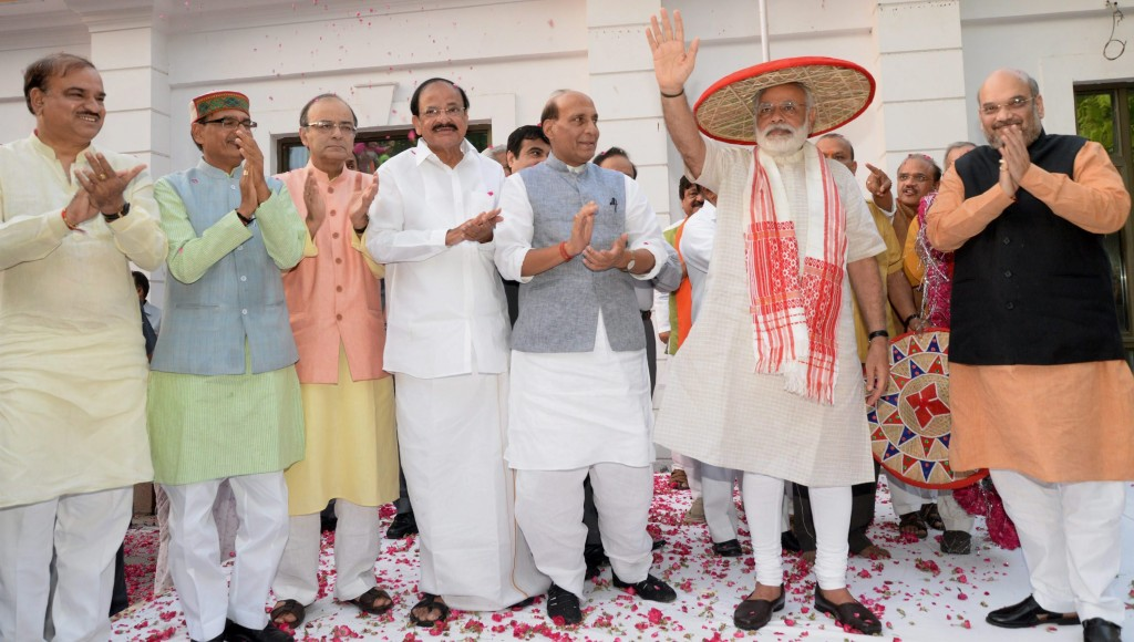 Prime Minister Narendra Modi waves at BJP workers after being presented an Assamese japi and gamosa to mark the party's victory in the Assam assembly polls on Thursday. Credit: PTI/Vijay Verma