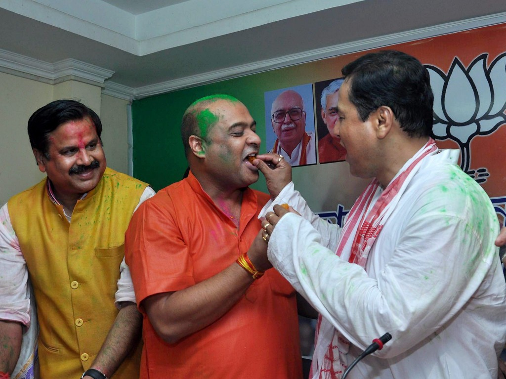 BJP chief ministerial candidate Sarbananda Sonowal exchanging sweets with party leader Himanta Biswa Sarma at a press conference after the party's win. Credit: PTI