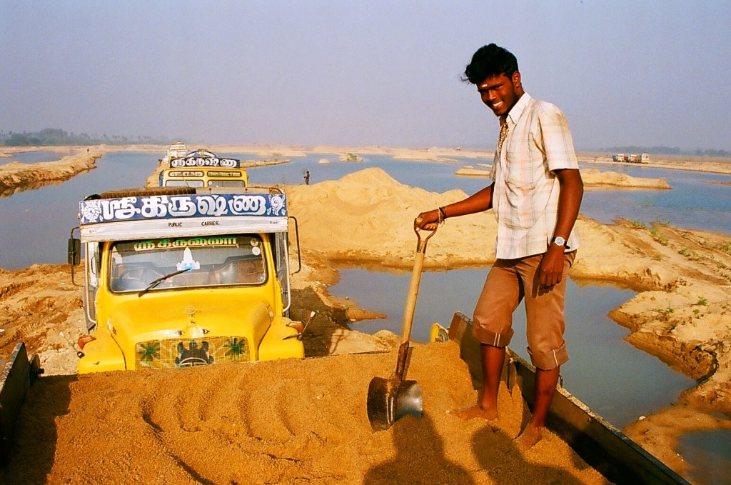 A truck driver loads sand onto his truck. Kanchipuram, Tamil Nadu.