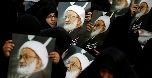 Supporters hold posters of Bahrain's leading Shi'ite cleric Isa Qassim during a sit-in outside his home in the village of Diraz west of Manama, Bahrain June 21. credit: Reuters/Hamad I Mohammed