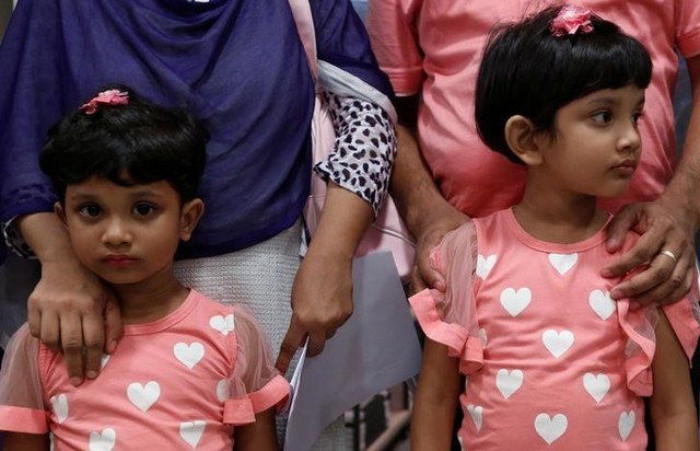 Shahzia (left), 5, and her sister Sanzida, 6, pose with their parents in Hong Kong June 16, 2016, after the family fled Bangladesh. Reuters/Bobby Yip