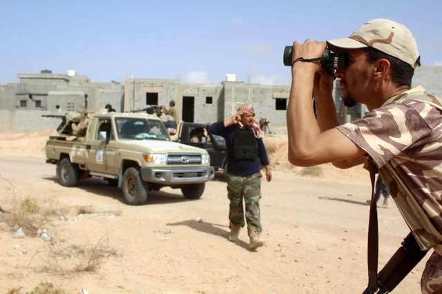 A fighter from forces aligned with Libya's new unity government monitors Islamic State locations at Algharbiyat area in Sirte, June 21. Credit: Reuters